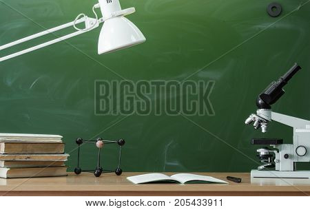 Teacher or student desk table. Education background. Education concept. Microscope copybook with pen lamp and stacked books on the table. Chemistry or biology lesson.