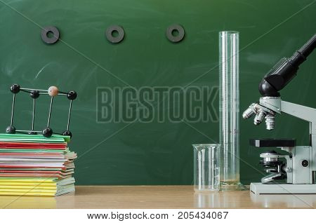 Teacher student biologist or chemist desk table. Education background with copy space. Education concept. Microscope vial flask beaker and stacked books on the table.