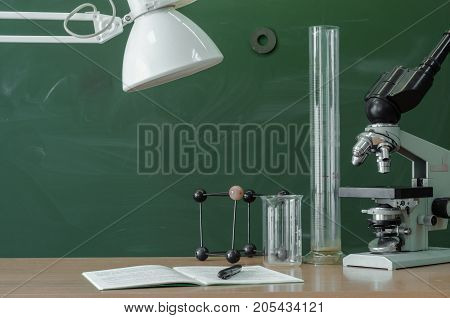 Teacher student biologist or chemist desk table. Education background. Education concept. Microscope vial flask beaker and book with pen and lamp on the table.