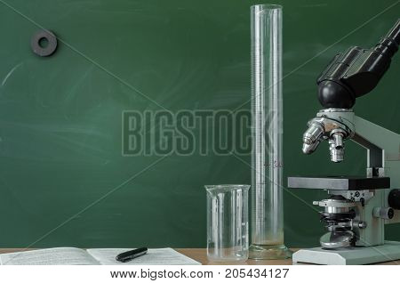 Teacher student biologist or chemist desk table. Education background. Education concept. Microscope vial flask beaker and book with pen on the table.
