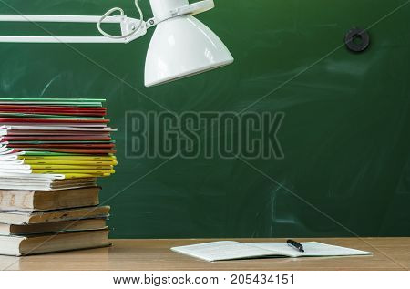 Teacher or student desk table. Education background. Education concept. Stacked books open book copybook handbook and lamp on the table.