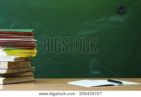 Teacher or student desk table. Education background. Education concept. Stacked books open book copybook handbook on the table.