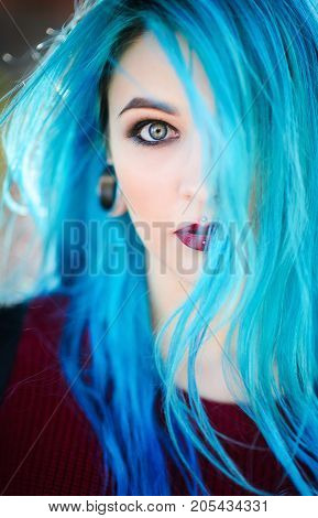 Closeup portrait of a beautiful young woman with blue hair