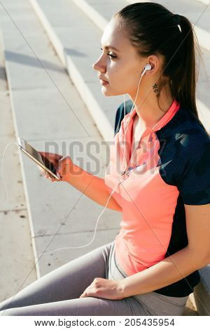 Young woman athlete runner listens to music on the smartphone