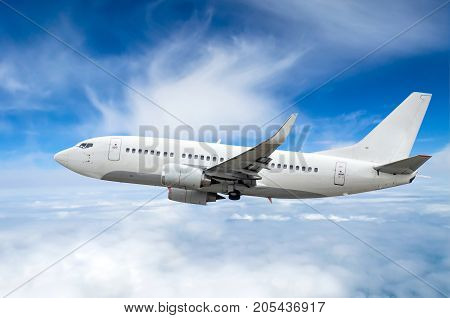 Passenger Airplane Flies On A Flight Level Against A Background Of Clouds And A Blue Sky