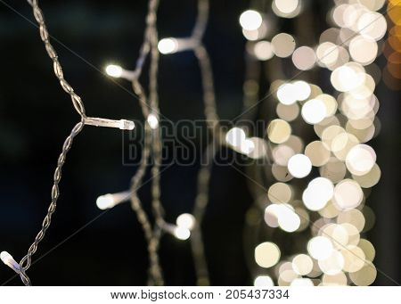 illumination, celebration, decoration concept. close up of one among a number twinkle lights sparkling on the blured backgroud of its radiant friends