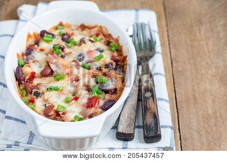 Baked rice casserole with different kinds of beans cheese and paprika in a white ceramic baking dish horizontal copy space