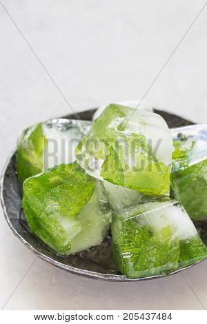 Homemade ice cubes with mint leaves inside on a metal plate ice for lemonade and cocktail vertical copy space