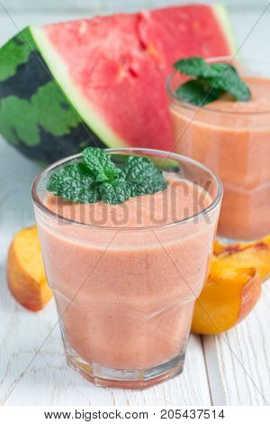 Watermelon peach mint and coconut milk smoothie in a glass on white wooden background vertical