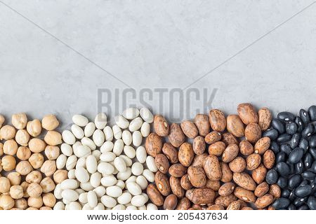 Different kinds of beans: black pinto white and chickpeas on concrete background copy space horizontal