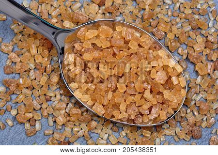 Sugar brown crystals in a spoon on slate close-up