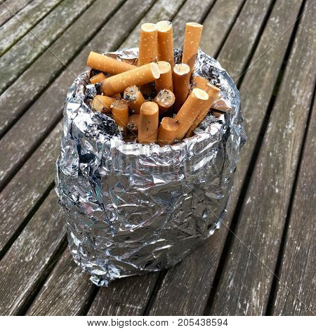 Full ashtray with cigarette butts on a wooden table
