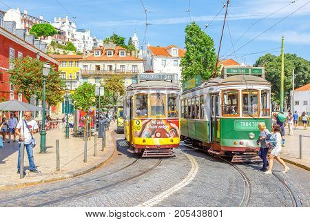 Lisbon, Portugal - August 25, 2017: new Tram Tour and famous vintage yellow Tram 28 near Portas do Sol viewpoint in historic Alfama District.Trams are icon of the Portuguese capital. Lisbon cityscape.