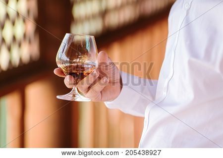 lifestyle, drinks, wealth concept. close up of dazzling glass with brandy, rathere hard liquor, that is held by man in elegant snowy white shirt with tidy manicure