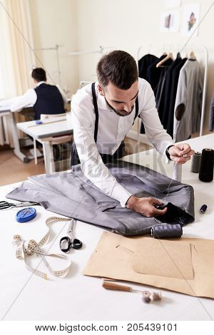 Interior of busy sewing atelier: concentrated young tailor sewing custom-made male jacket by hands while his colleague cutting out fabric