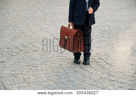Close up shot of future businessman holding leather briefcase while staying on pavage street outdoor in city. Braun leather bag with golden belt on gray stone background. Copy space available.