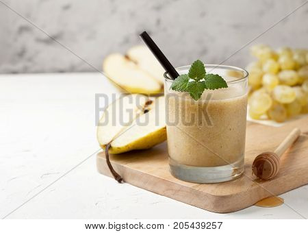 Smoothies of pears and grapes in a glass on a white background concrete