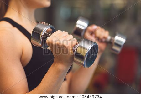 Young Fitness Girl Lifting Dumbbells In The Gym