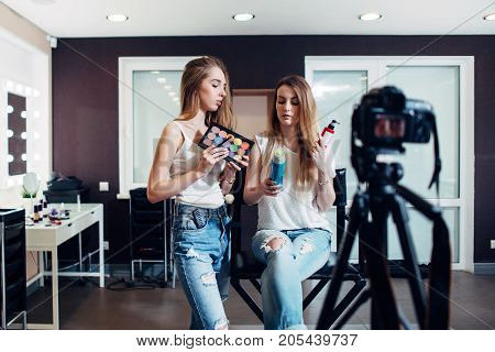 Two beauty bloggers doing make-up and haircare products review filming it on camera for their vlog.