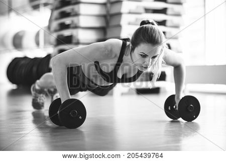 Young Strong Girl Doing Push-ups On Dumbbells In The Gym. Black And White Photo