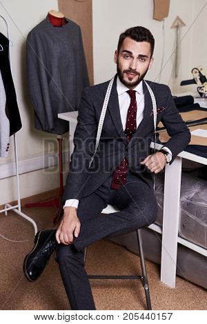Full length portrait of stylish young fashion designer in suit looking at camera while sitting on chair, interior of modern studio on background