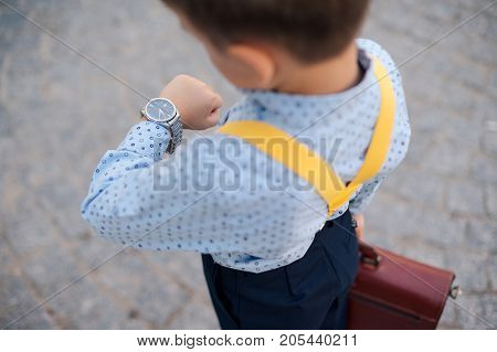 Concept future businessman. Boy portrait in dark blue pants, baby blue shirt and yellow suspenders, standing on pedestrian street with braun briefcase looking to his watch, urban background.