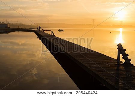 Unusual orange sunrise over the lake. The sun and the sunny path. Clouds are reflected on the water surface. Silhouettes of people on the wooden pier. Boat with fishermen. High-voltage lines in the background