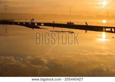 Unusual orange sunrise over the lake. The sun and the sunny path. Clouds are reflected on the water surface. Silhouettes of people on the pier. Boat with fishermen. High-voltage lines in the background
