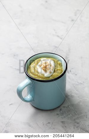 green soup puree with cream pine nuts in a blue cup on a gray concrete background.