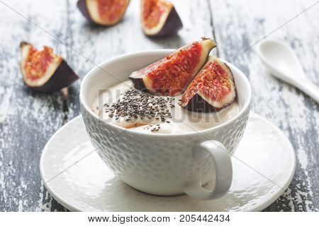 yogurt with figs chia seeds and honey in a white cup on old wooden background