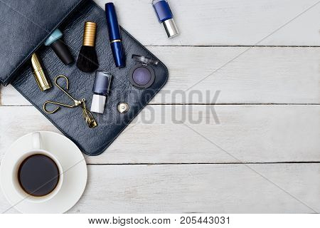 Female handbag of dark blue color and cosmetics with cup of coffee