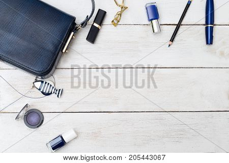 Female handbag of dark blue color and cosmetics on a wooden background. Copy space