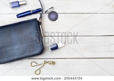 Small female handbag of dark blue color and cosmetics on a wooden background