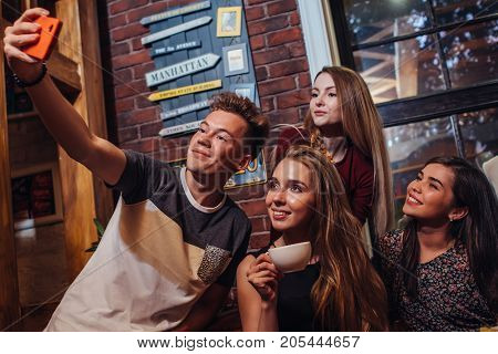 Group of smiling attractive teenagers wearing casual outfit taking selfie with mobile phone drinking tea in a cafe with loft interior.