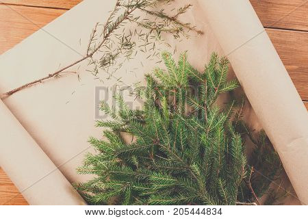 Prepare for christmas eve or other winter holidays. Xmas decorations, fir tree branches on present packaging paper concept background, top view on wood.