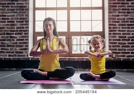 Mother and daughter smiling while doing yoga exercises sitting in Padmasana relaxing on mat at home.