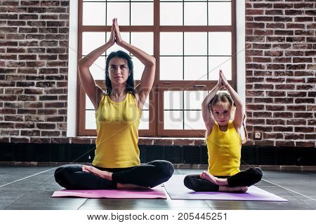 Female yoga instructor training little girl doing stretching exercise sitting in lotus position indoors.