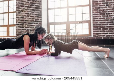 Mother and daughter standing in dolphin plank pose, phalankasana, during yoga session in fitness center.