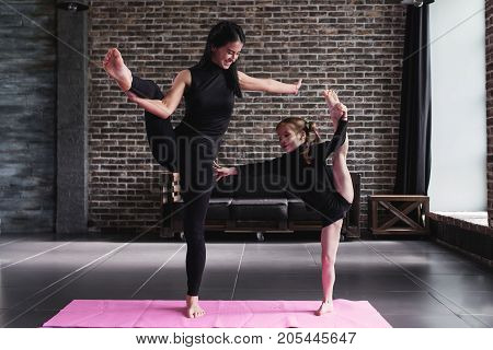 Cute little child girl and adult woman doing standing split balance gymnastic exercise in a living room.