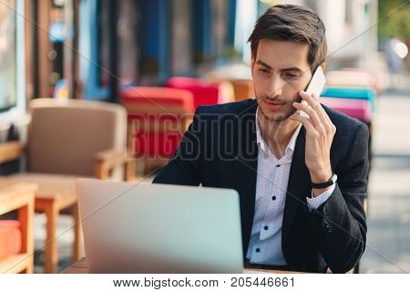 Multitasking. Young businessman working on laptop and talking on phone, at the table on colorful cafe terrace. Ambitious freelancer, in casual jacket, unbuttoned shirt typing, looking to laptop screen