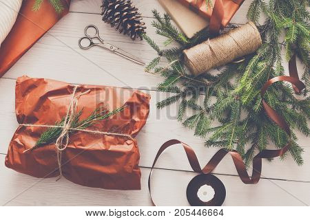 Gift wrapping background. Packaging sweater as christmas present in maroon paper decorated with satin ribbon. Winter holidays concept. Top view of white wood table with fir tree branches