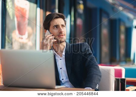 Multitasking. Young businessman working on laptop and talking on phone, at the table on colorful cafe terrace. Ambitious freelancer, in casual jacket, unbuttoned shirt typing, looking to left.