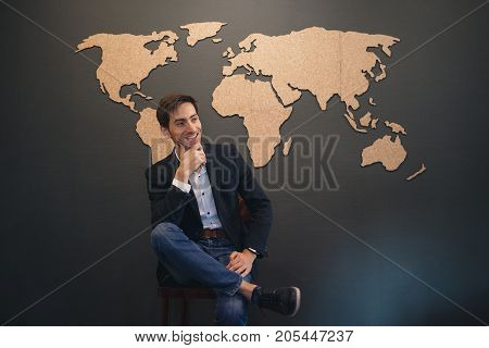 Young man dreaming big. Dreams to travel all over the world. Casual man sitting on a chair smiling holding chin with arm and having leg over leg, looking to right against world map on wall background.