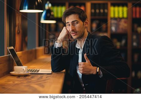 Portrait man resting his head on arm sitting at wooden table in modern cafe. Indifferent man in jacket and shirt posing while looking to camera and showing OK thumb up, with cup of coffee and laptop.