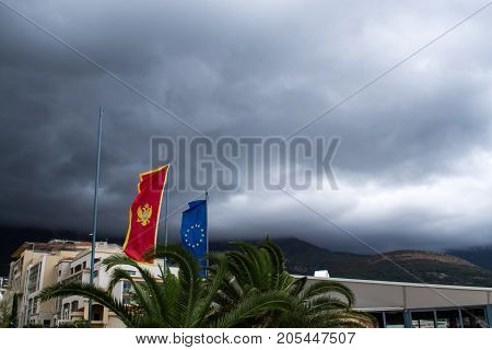 Flags of Montenegro and the European Union against the backdrop of dark clouds. Montenegro. The Budva Riviera