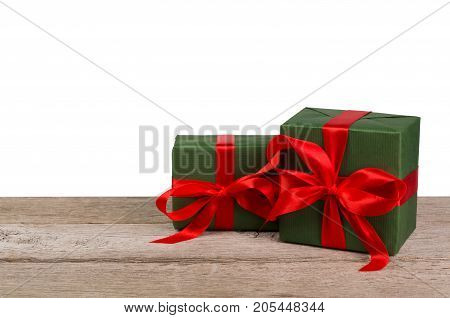 Two gift boxes wrapped with green paper and red satin ribbon on wooden table at white background. Modern presents for any holiday, christmas, valentine or birthday