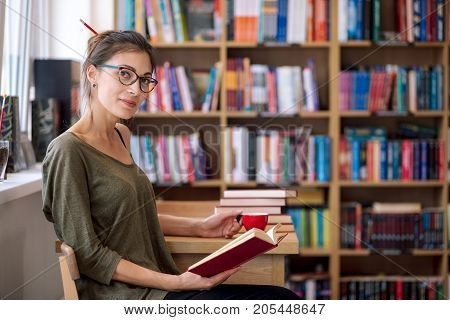 Beautiful young lady wearing fashionable glasses is reading a book  and holding a coffee cup in her hand while sitting at a wooden table with a stack of books on it, near bookshelf, looking to camera.