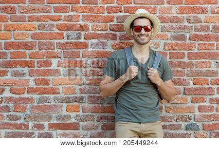 Outdoor Portrait Of Young Caucasian Man Pictured With Red Brick Wall In Background Looking Through S