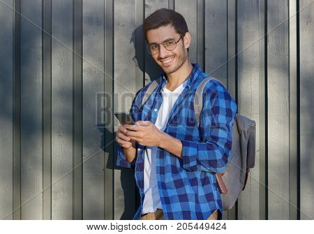 Outdoor Closeup Of Young Positive European Guy Standing Against Gray Wooden Fence Background Wearing