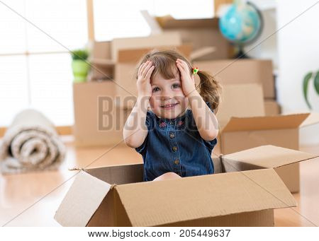 Child girl looking out of a box in new room after moving